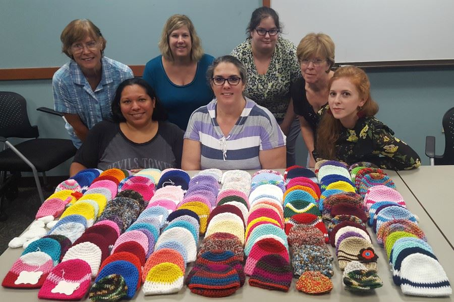 Women smiling in front of their crocheted hats